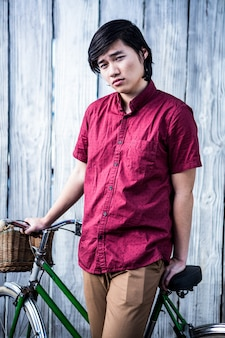 Hipster homem segurando uma bicicleta