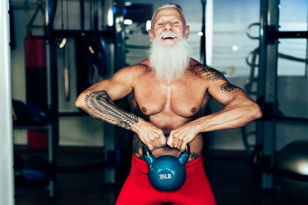 Hipster homem sênior treinamento dentro da academia - pessoa tatuada madura se divertindo fazendo exercícios de treino no clube de fitness esporte