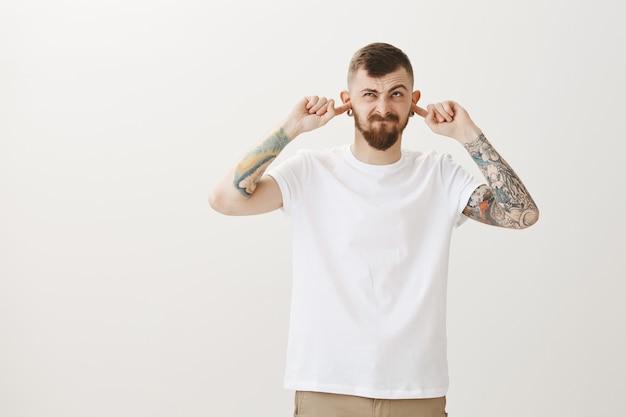 Hipster irritado fecha os ouvidos e olha para cima, ouve barulho
