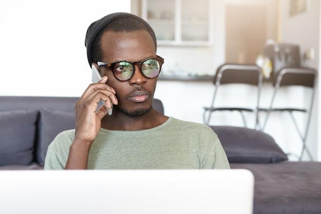 Hipster jovem atraente em elegantes óculos e chapelaria, tendo um olhar sério e pensativo enquanto fala no smartphone, usando a conexão de internet sem fio no laptop no lobby do hotel