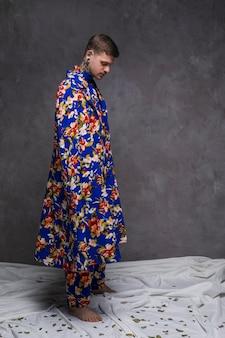 Hipster jovem em floral longo drape olhando folhas caindo em pano branco contra parede cinza