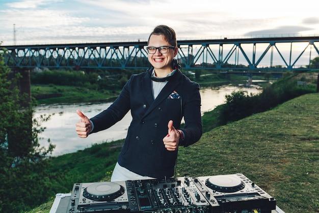 Hipster jovem em um terno azul com fones de ouvido levanta os dedos