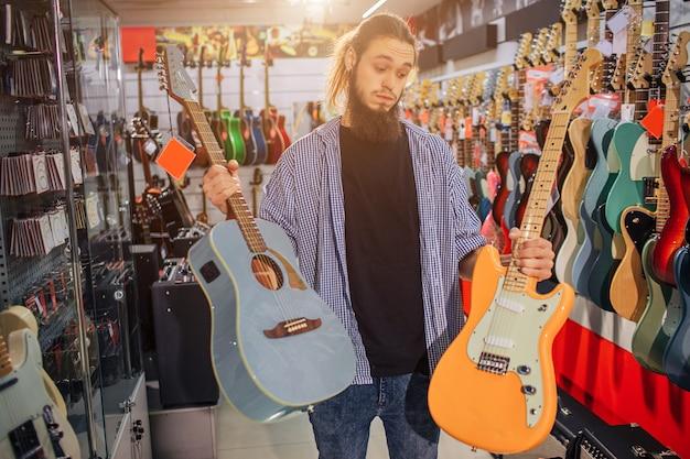 Hipster jovem ficar e segurar guitarras elétricas e acústicas. ele olha para o amarelo. o cara não pode escolher entre dois instrumentos.