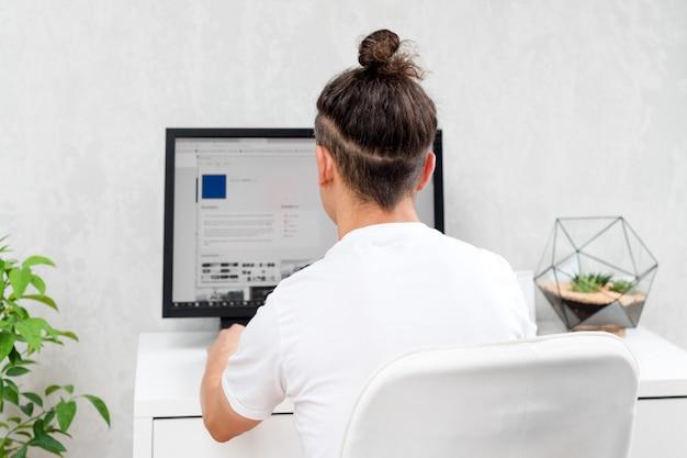 Hipster jovem usando o computador, sentado no espaço loft. programador digitando código de dados, trabalhando em projeto na empresa de desenvolvimento de software.