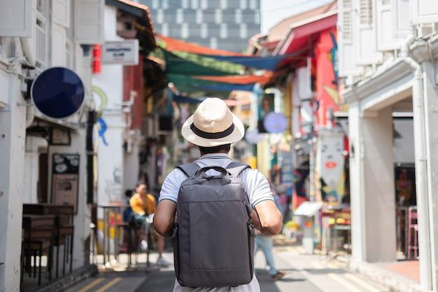Hipster jovem viajando com mochila e chapéu