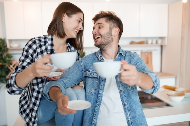 Hipster legal jovem feliz e mulher na cozinha, café da manhã, casal pela manhã, sorrindo, tomando chá