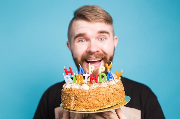 Hipster louco engraçado positivo segurando um bolo de feliz aniversário nas mãos, de pé sobre uma parede azul
