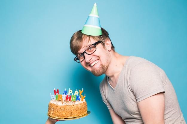 Hipster louco engraçado positivo segurando um bolo de feliz aniversário nas mãos, de pé sobre uma superfície azul