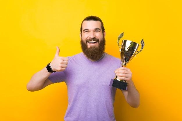 Hipster masculino alegre está segurando um troféu e mostrando como um gesto.