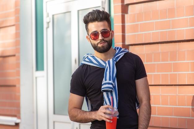 Hipster masculino jovem árabe elegante bonito com um bigode e uma barba e usando óculos, bebendo suco com um canudo. conceito de férias de verão.