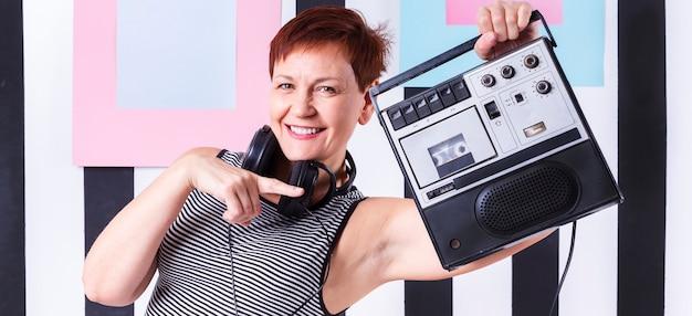 Hipster mulher sênior mostrando um toca-fitas vintage
