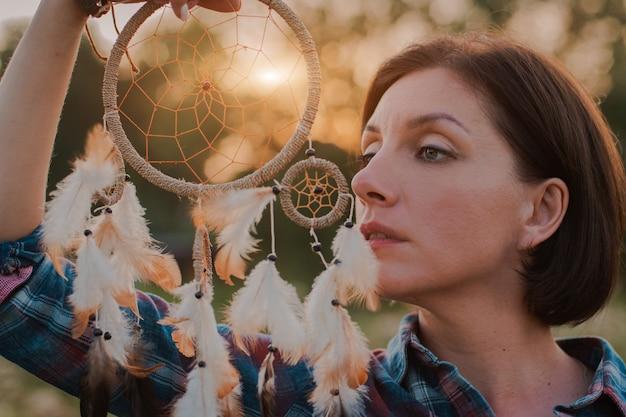 Hipster mulher sob a forma de um xamã está à procura de inspiração da mãe terra em um wigwam na natureza.