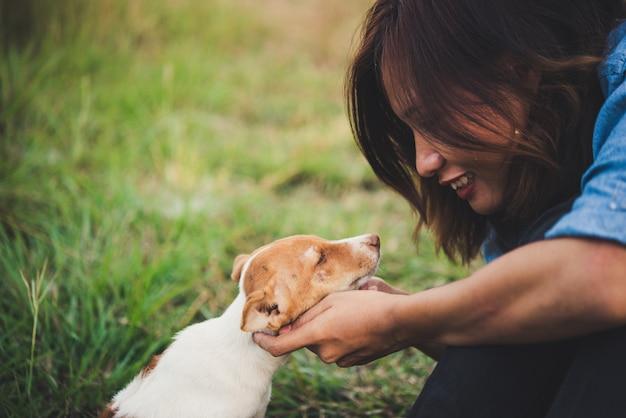 Hipster mulher sorriso gostar de brincar com seu filhote de cachorro no campo do verão, filtro de tons vintage.