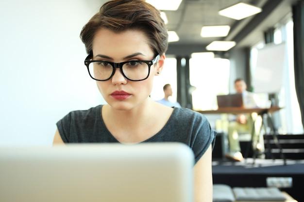 Hipster mulher usa laptop enorme loft studio.student pesquisando processo de trabalho. young business team working creative startup moderno office.analyze estoque de mercado, nova estratégia. turva, efeito de filme.