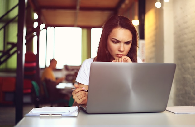 Hipster mulher usar laptop enorme loft studio.student pesquisando processo de trabalho.