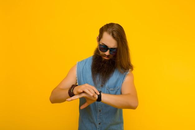 Hipster olhando a hora em seu relógio de pulso contra um fundo amarelo.