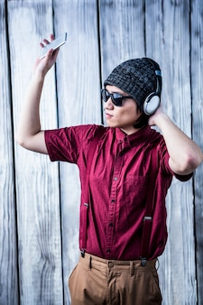 Hipster ouvir música com auscultadores, mantendo um smartphone