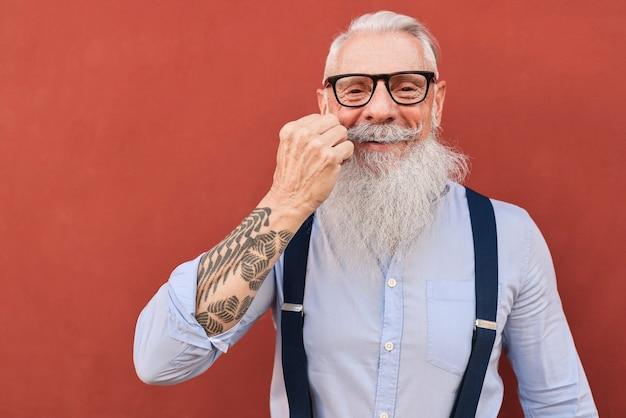 Hipster sênior feliz tocando o bigode com uma parede vermelha
