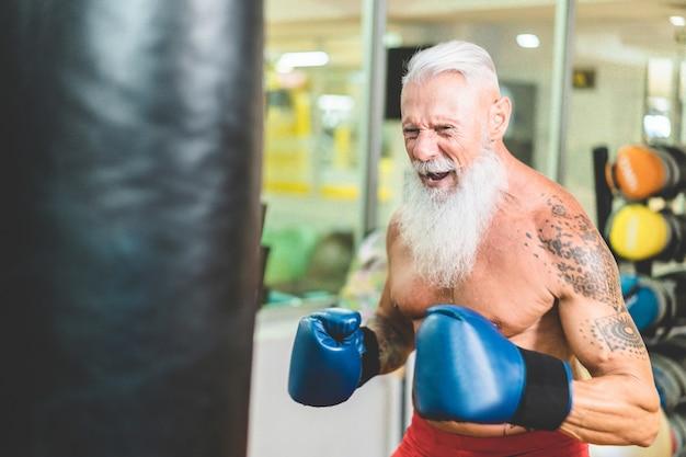 Hipster sênior homem boxe dentro de clube de ginástica fitness fitness