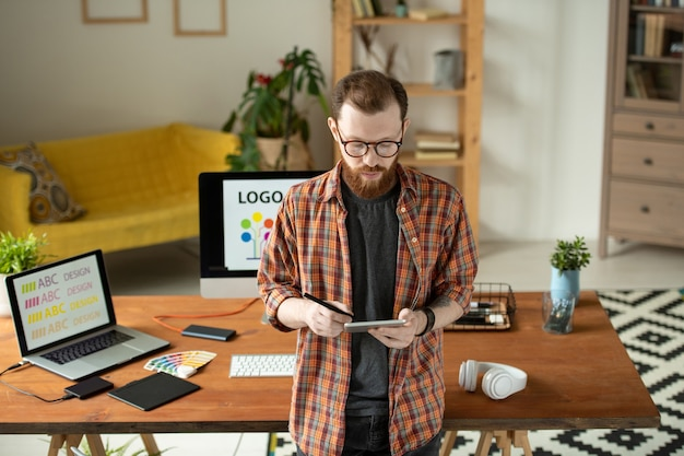 Hipster sério barbudo designer usando óculos usando uma caneta enquanto verifica o esboço no tablet em um escritório doméstico aconchegante