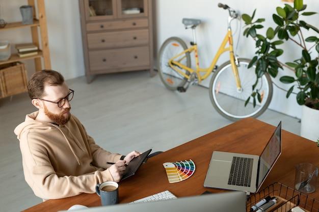 Hipster sério jovem designer gráfico em óculos, sentado à mesa no escritório em casa com uma bicicleta e trabalhando em um tablet digitalizador