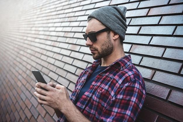 Hipster sms aplicativo de telefone de mensagens de texto na rua da cidade, na superfície da parede de tijolos. homem incrível segurando o smartphone em pé de smart casual wear. estilo de vida profissional jovem urbano.