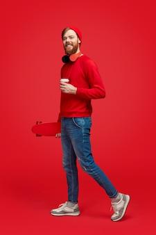 Hipster sorridente com bebida e skate