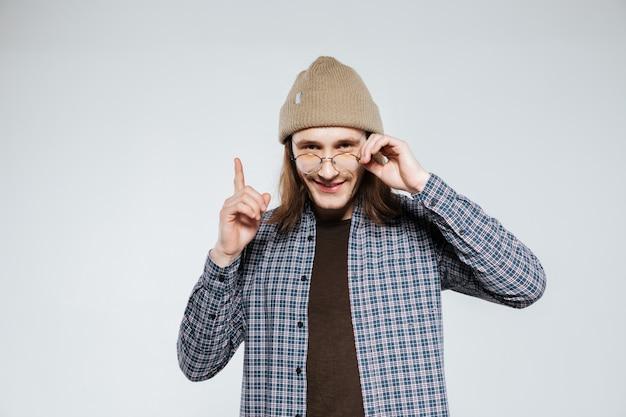 Hipster sorridente em óculos, apontando para cima