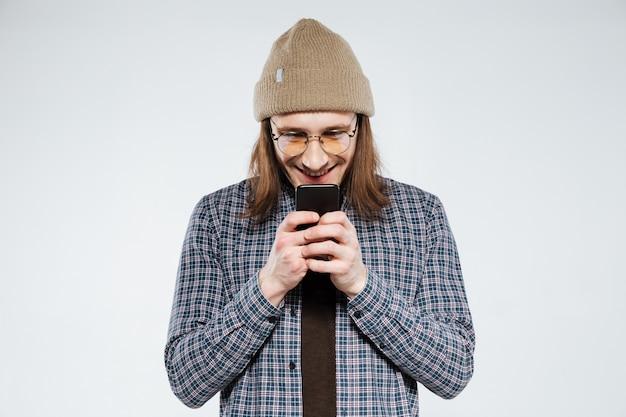 Hipster sorridente em óculos usando smartphone