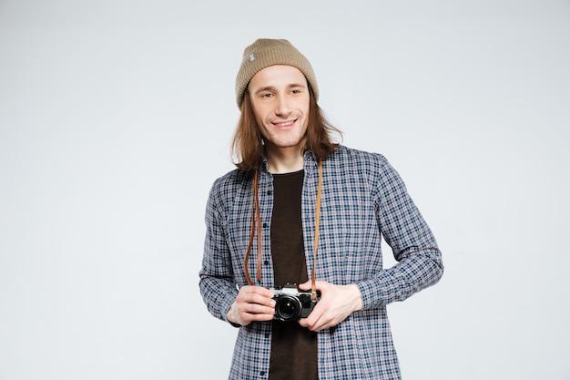Hipster sorridente segurando a câmera retro