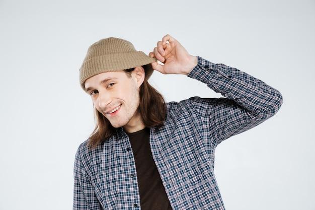 Hipster sorridente segurando o chapéu e ouvir