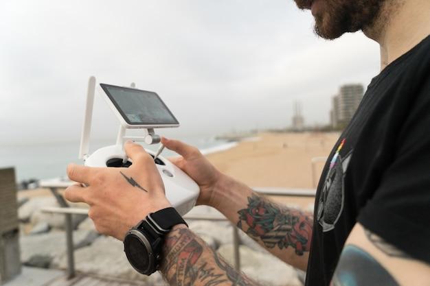 Hipster tecnologicamente experiente ou fotógrafo profissional milenar da geração jovem usa o controle remoto para pilotar drone ou quadrocóptero no ar
