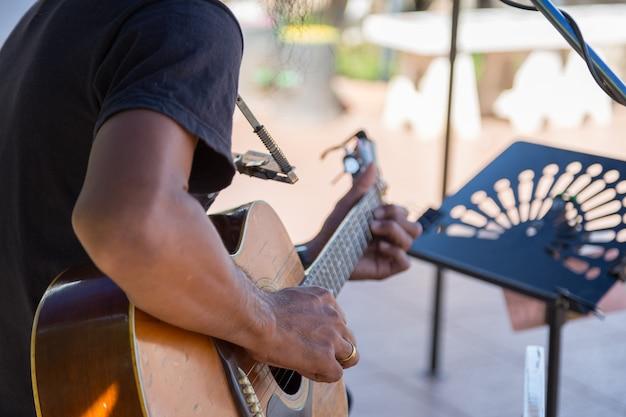 Hipster tocando uma guitarra de madeira velha em feliz momento com desfocar o fundo