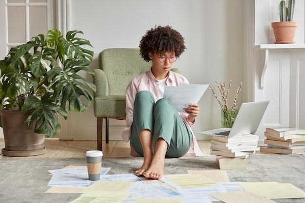 Hipster trabalhadora de pele escura séria espera a instalação da atualização no laptop, senta no chão com muitos papéis