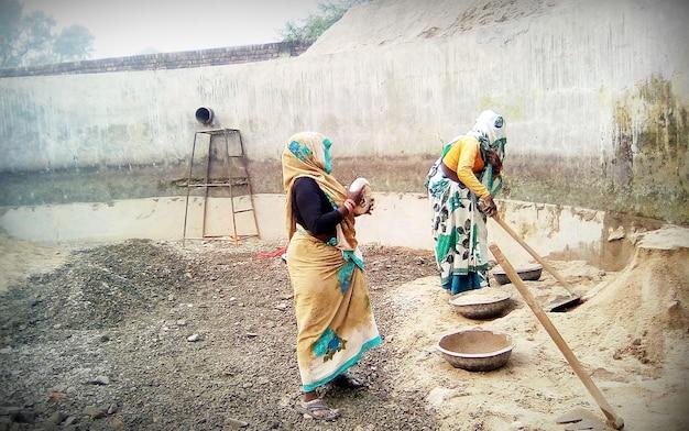 Hisar, haryana, índia - setembro de 2018: trabalhos indianos misturando material de construção no canteiro de obras