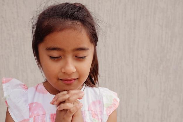 Hispânico menina criança rezando, conceito de fé de cristianismo