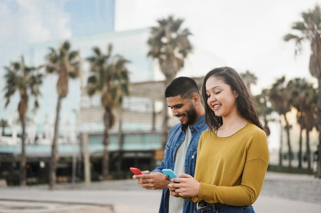 Hispânicos usando celular ao ar livre na cidade
