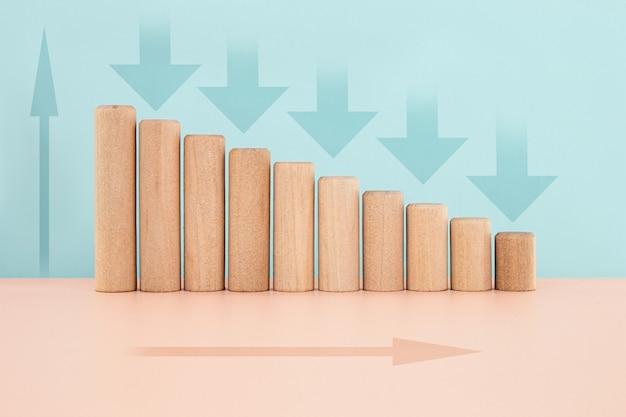 Histograma do gráfico de blocos de madeira ou gráfico de barras infográficos com a seta para baixo em fundo azul