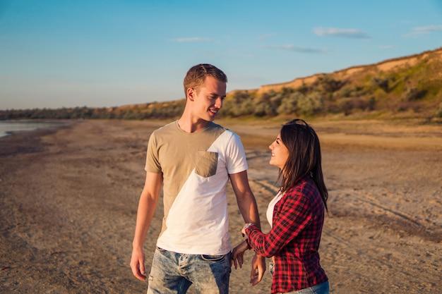 História adorável de um jovem casal lindo na praia no pôr do sol