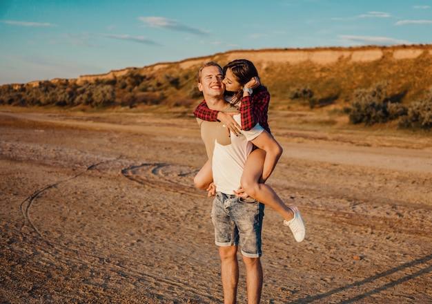 História adorável de um jovem lindo casal pegando carona na praia no pôr do sol