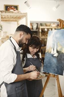 História de amor de um casal adulto em um estúdio de arte. eles pintam quadros, riem, se beijam. suas emoções, sentimentos, amor.
