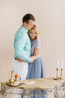 História de amor jovem e homem são ficar e de mãos dadas no interior vintage. mesa com pernas forjadas e castiçal com velas.