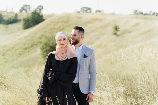 História de amor muçulmana de casal misto. homem e mulher sorriem e caminham nas colinas verdes.
