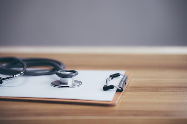 História médica com estetoscópio e prancheta na mesa de madeira