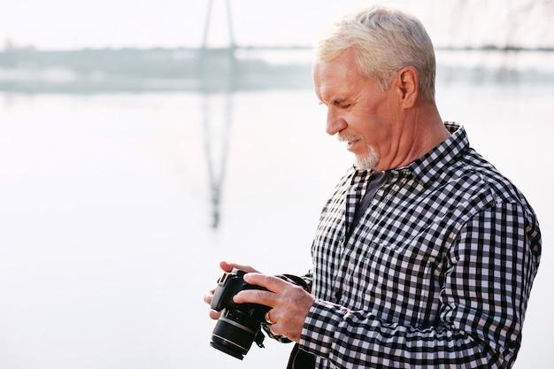História não escrita. homem maduro meditativo segurando uma câmera e olhando para baixo
