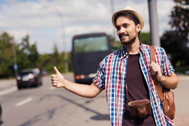 Hitchhiker catches car homem viaja com a câmera.