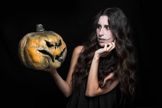 Hitchy mulher segurando a abóbora de halloween