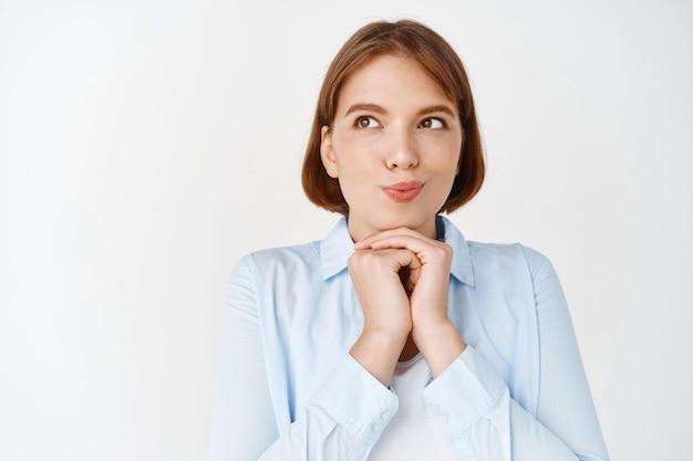 Hmm, deixe-me pensar. garota sonhadora e pensativa imaginando coisas, dedos curvos e olhando para o lado com rosto intrigado, em pé com uma blusa na parede branca