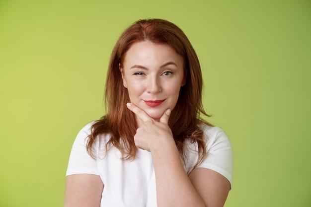 Hmm escolha interessante intrigado astuto ruiva mulher de meia idade segurar mão rosto esfregar o queixo pensativo sorrindo satisfeito levantar sobrancelha curioso ponderando decisão atraente parede verde