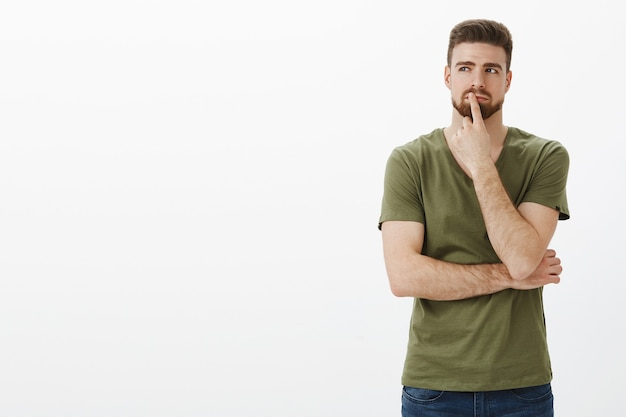 Hmm, pode funcionar. retrato de um homem fazendo um plano e tomando uma decisão em mente, parado em uma pose pensativa, tocando o lábio com o dedo enquanto pensa, olhando determinado no canto superior esquerdo, escolhendo